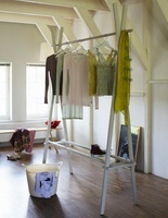 Clothes hanging on a homemade clothes rack in a white-painte
