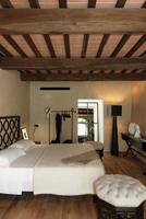 An elegant bedroom beneath a rustic wooden beam ceiling in a 20052011530| 写真素材・ストックフォト・画像・イラスト素材|アマナイメージズ