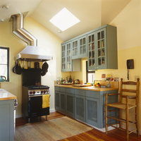 Country kitchen with blue wooden units and free-standing coo 20052013421| 写真素材・ストックフォト・画像・イラスト素材|アマナイメージズ