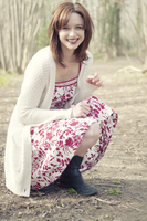 Relaxed portrait of smiling young woman in summer dress and cardigan in sunny Autumn woods 20055017635| 写真素材・ストックフォト・画像・イラスト素材|アマナイメージズ