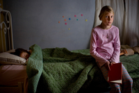 Girl sitting at the edge of her sister's bed with a book. 20055019726| 写真素材・ストックフォト・画像・イラスト素材|アマナイメージズ