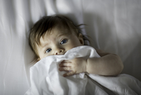 Young baby peeking out from under sheet. 20055021046| 写真素材・ストックフォト・画像・イラスト素材|アマナイメージズ