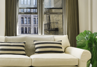 White Couch With Pillows And View Out Safety Glass Facing Fire Escape And Old Building 20055022315| 写真素材・ストックフォト・画像・イラスト素材|アマナイメージズ