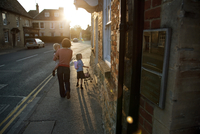 Late evening shot of a mother with her children walking along a village high street 20055030763| 写真素材・ストックフォト・画像・イラスト素材|アマナイメージズ