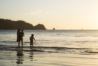 mother and two sons standing in the ocean with backlit costa rican shoreline behind them at sunset 20055032024| 写真素材・ストックフォト・画像・イラスト素材|アマナイメージズ