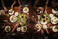 Aerial view of a table of people sharing a meal in a dimly lit space. 20055032990| 写真素材・ストックフォト・画像・イラスト素材|アマナイメージズ