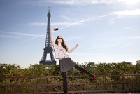 Young woman balancing on one leg with mobile phone taking selfie, Eiffel Tower in background 20055034619| 写真素材・ストックフォト・画像・イラスト素材|アマナイメージズ