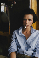 Serious portrait of a brown haired girl smoking a cigarette in a denim shirt. 20055034834| 写真素材・ストックフォト・画像・イラスト素材|アマナイメージズ