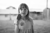 Portrait of young girl eating a messy chocolate covered ice cream popsicle with chocolate and ice cream on her face in her famil 20055034885| 写真素材・ストックフォト・画像・イラスト素材|アマナイメージズ