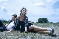 In the countryside a young couple recline on the grass field. 20055035003| 写真素材・ストックフォト・画像・イラスト素材|アマナイメージズ