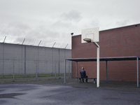 A prisoner sit on a bench in the prison courtyard, his back to the camera. 20055035588| 写真素材・ストックフォト・画像・イラスト素材|アマナイメージズ