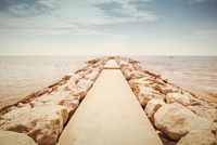 A concrete jetty surrounded by rocks leads to the sea 20055035646| 写真素材・ストックフォト・画像・イラスト素材|アマナイメージズ