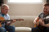 Grown-up father and son play guitar together