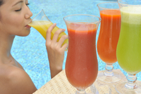 Young woman in a swimming pool sipping one of a selection of fruit juices 20062010501| 写真素材・ストックフォト・画像・イラスト素材|アマナイメージズ