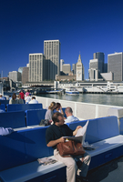 Man reading newspaper and passengers on the commuter ferry, with Ferry Building and skyline of downtown San Francisco in the bac 20062018827| 写真素材・ストックフォト・画像・イラスト素材|アマナイメージズ