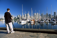 Photographer at False Creek marina, with downtown skyscrapers behind, Vancouver, British Columbia (B.C.), Canada, North America 20062019044| 写真素材・ストックフォト・画像・イラスト素材|アマナイメージズ