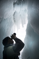 Tourist framed in the frozen mouth of ice cave, with icicles formed on roof of caves at Olkhon Island as the waves freeze in win 20062022150| 写真素材・ストックフォト・画像・イラスト素材|アマナイメージズ