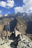 Man hiking in Tiger Leaping Gorge, UNESCO World Heritage Site, with Jade Dragon Snow Mountain (Yulong Xueshan), Yunnan, China, A 20062063901| 写真素材・ストックフォト・画像・イラスト素材|アマナイメージズ