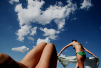 View from below of blue skies, small white clouds, girls legs and another girl in green bikini laying her sarong on the beach. B 20071005053| 写真素材・ストックフォト・画像・イラスト素材|アマナイメージズ
