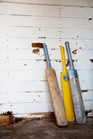Two old wooden cricket bats and one plastic yellow cricket bat leaning against an old white weatherboard wall 20071005164| 写真素材・ストックフォト・画像・イラスト素材|アマナイメージズ