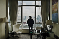 Rear view of man standing alone in a hotel room looking out of a window. Hong Kong, China 20071009500| 写真素材・ストックフォト・画像・イラスト素材|アマナイメージズ