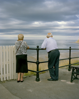 Couple lean over a railing staring out to sea while heavy clouds pass over. Saltburn, Teeside, England, United Kingdom 20071010905| 写真素材・ストックフォト・画像・イラスト素材|アマナイメージズ