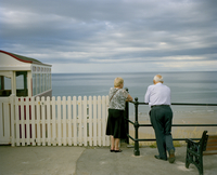 Couple lean over a railing staring out to sea while heavy clouds pass over. Saltburn, Teeside, England, United Kingdom 20071010906| 写真素材・ストックフォト・画像・イラスト素材|アマナイメージズ