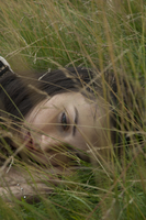 Young woman lying in long grass in summer looking down. London, England, United Kingdom 20071011719| 写真素材・ストックフォト・画像・イラスト素材|アマナイメージズ