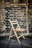 A folding wooden chair left on the pavement by a brick wall 20071011725| 写真素材・ストックフォト・画像・イラスト素材|アマナイメージズ