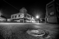 Low angle night time street scene of corner building with man hole in foreground. Johannesburg, South Africa 20071011751| 写真素材・ストックフォト・画像・イラスト素材|アマナイメージズ