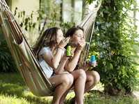 Two girls sitting on a stripy hammock outside blowing bubbles 20071011794| 写真素材・ストックフォト・画像・イラスト素材|アマナイメージズ