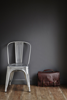 Contemporary metal chair with a brown leather briefcase leaning against a grey painted wall 20071011810| 写真素材・ストックフォト・画像・イラスト素材|アマナイメージズ