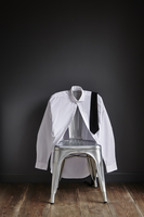 White shirt and black tie hung over the back of a contemporary metal chair against a grey painted wall 20071011812| 写真素材・ストックフォト・画像・イラスト素材|アマナイメージズ