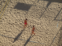 Two women with playing volley ball on the beach. Marseille, France