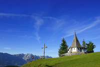 Hikers on the summit of power Alm chapel in the background of the Wilder Kaiser, Hohe Salve, Itter, Kitzbuhel Alps, Tyrol, Austr
