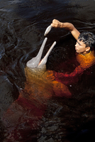 South America, Brazil, Amazonas, A boy feeding an Amazon river dolphin fish on a creek in the Rio Negro in the Anavilhanas islan 20088002124| 写真素材・ストックフォト・画像・イラスト素材|アマナイメージズ