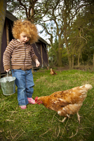 Bedfordshire, England. A little girl feeds the chickens while glamping. MR 20088007206| 写真素材・ストックフォト・画像・イラスト素材|アマナイメージズ