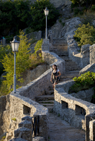 Europe, San Marino. Young woman walking down the steps of one of the three castles overlooking the city on Monte Titano. MR. UNE 20088042230| 写真素材・ストックフォト・画像・イラスト素材|アマナイメージズ