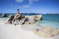 Woman sitting on rocks on Nishibama Beach, Aka Island, Kerama Islands, Okinawa, Japan (MR) 20088049430| 写真素材・ストックフォト・画像・イラスト素材|アマナイメージズ