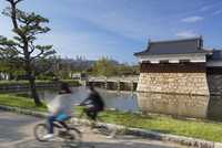 People cycling past tower and moat of Hiroshima castle, Hiroshima, Hiroshima Prefecture, Japan 20088049954| 写真素材・ストックフォト・画像・イラスト素材|アマナイメージズ