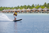 Maldives, Rasdhoo Atoll, Kuramathi Island. A man monoskis past water villas at Kuramathi Island Resort. MR. 20088054256| 写真素材・ストックフォト・画像・イラスト素材|アマナイメージズ