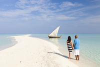 Maldives, Rasdhoo Atoll, Kuramathi Island. A couple on honeymoon stand looking at a traditional Maldivian Dhow on the sandbank a 20088054275| 写真素材・ストックフォト・画像・イラスト素材|アマナイメージズ