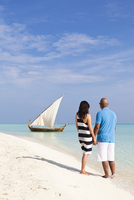Maldives, Rasdhoo Atoll, Kuramathi Island. A couple on honeymoon stand looking at a traditional Maldivian Dhow on the sandbank a 20088054276| 写真素材・ストックフォト・画像・イラスト素材|アマナイメージズ
