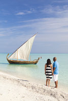 Maldives, Rasdhoo Atoll, Kuramathi Island. A couple on honeymoon stand looking at a traditional Maldivian Dhow on the sandbank a 20088054277| 写真素材・ストックフォト・画像・イラスト素材|アマナイメージズ