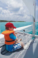 Maldives, Rasdhoo Atoll, Kuramathi Island. A young boy helps to sail a catamaran off Kuramathi Island Resort. MR. 20088054283| 写真素材・ストックフォト・画像・イラスト素材|アマナイメージズ