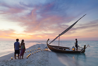 Maldives, Rasdhoo Atoll, Kuramathi Island. A couple wait to board a traditional Dhoni on the sandbank at Kuramathi Island Resort 20088054288| 写真素材・ストックフォト・画像・イラスト素材|アマナイメージズ
