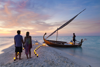 Maldives, Rasdhoo Atoll, Kuramathi Island. A couple wait to board a traditional Dhoni on the sandbank at Kuramathi Island Resort 20088054289| 写真素材・ストックフォト・画像・イラスト素材|アマナイメージズ