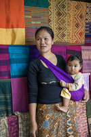 Laos, Ban Muangkeo, Luang Prabang, Luang Prabang Province. A woman holds her baby daughter in a sling beside her display of home 20088055550| 写真素材・ストックフォト・画像・イラスト素材|アマナイメージズ