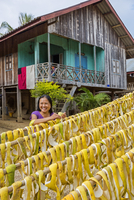 Nong Khiaw, Luang Prabang Province. A smiling woman hangs grapefruit peel out to dry in front of her house.  The peel will be ma