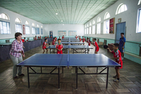A foreign tourist playing table tennis with students at the Dok Song Primary School, North Korea 20088061436| 写真素材・ストックフォト・画像・イラスト素材|アマナイメージズ